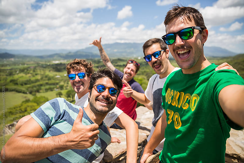 Group of young friends wearing sunglasses taking a selfie picture on a sunny day in a lookout by Alejandro Moreno de Carlos for Stocksy United
