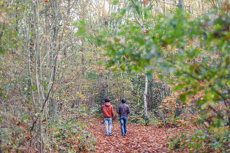 Father and son walking in the woods in autumn by Cindy Prins for Stocksy United