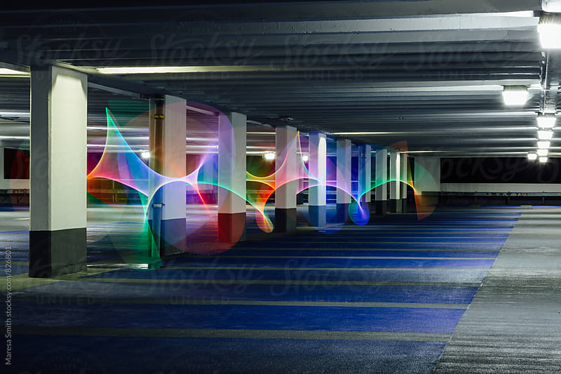 Rainbow swirls of light weaving around pillars in a dark car park by Maresa Smith for Stocksy United
