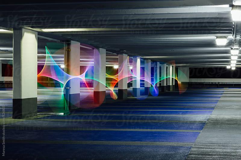 Rainbow swirls of light weaving around pillars in a dark car park by Maresa Smith for Stocksy United
