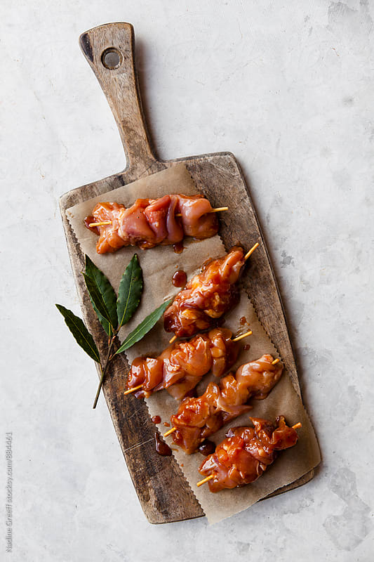 Chicken kebab skewers with marinade basting and bay leaves by Nadine Greeff for Stocksy United