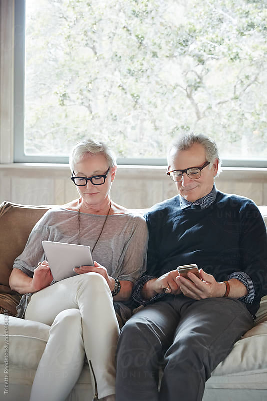 Mature couple with grey hair looking at digital tablet and phone at home by Trinette Reed for Stocksy United