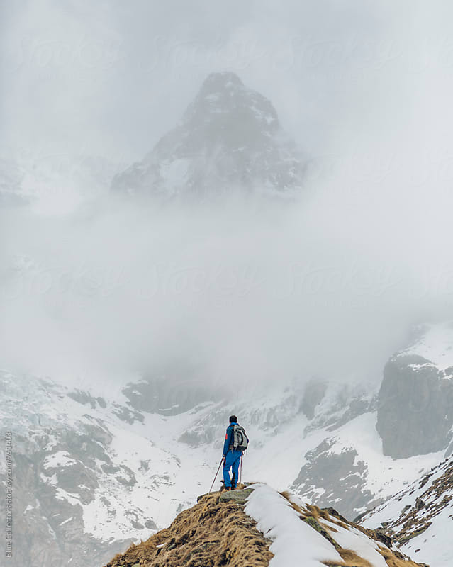 Young alpine climber with blue dress looking from the viewpoint glacier in the Italian Alps by Jordi Rulló for Stocksy United