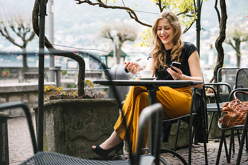 Young beautiful blonde woman sitting at cafe by GIC for Stocksy United