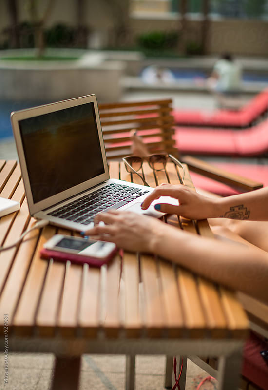 Woman Working on a Laptop by the Swimming Pool by Mosuno for Stocksy United