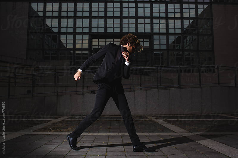 Young businessman dancing outdoors by michela ravasio for Stocksy United