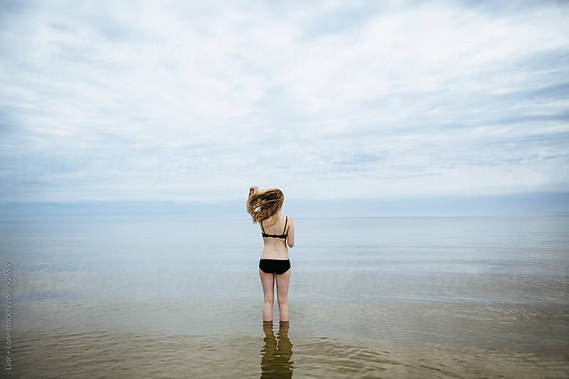 Blond woman in bathing suit standing in water by Lior + Lone for Stocksy United