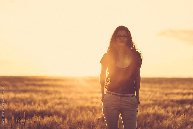 young woman in a field at sunset by Javier Pardina for Stocksy United