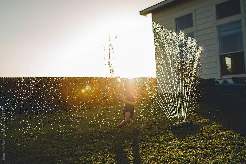 toddler running through sprinkler by Courtney Rust for Stocksy United