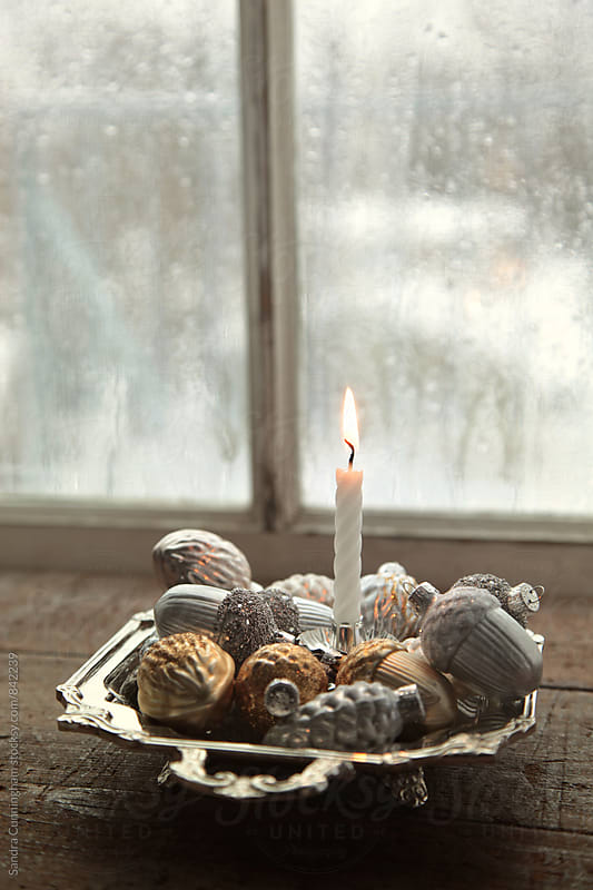Small candle surrounded by Christmas ornaments on tray by Sandra Cunningham for Stocksy United