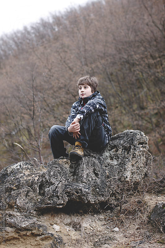 Young boy sitting on the rock by Bratislav Nadezdic for Stocksy United