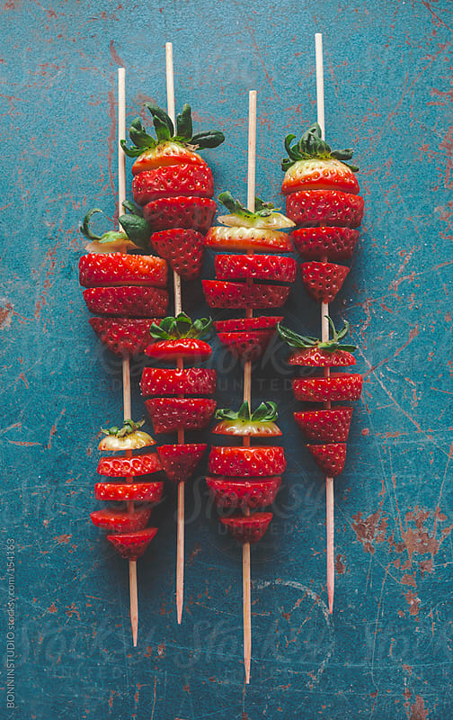 Brochete of cuted strawberries on blue background.  by BONNINSTUDIO for Stocksy United