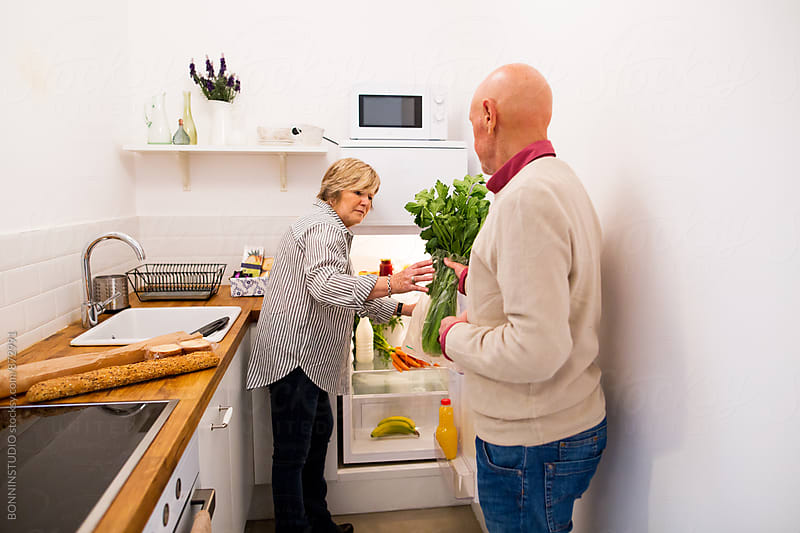 Elderly couple putting organic food into the fridge. by BONNINSTUDIO for Stocksy United