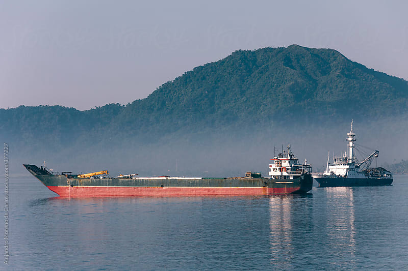 Cargo ships on the sea with mountain on background by Alejandro Moreno de Carlos for Stocksy United