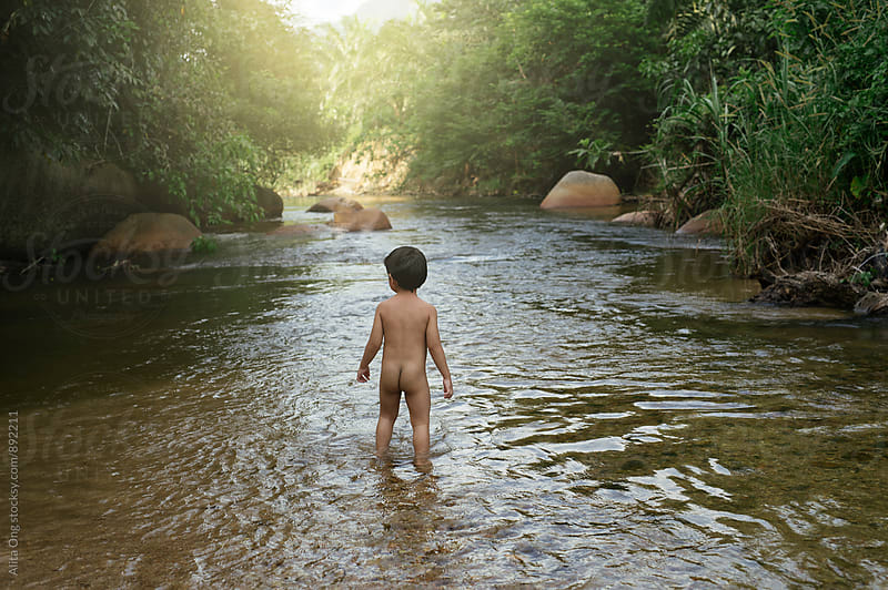 Little boy goes au naturel in a creek by Alita Ong for Stocksy United