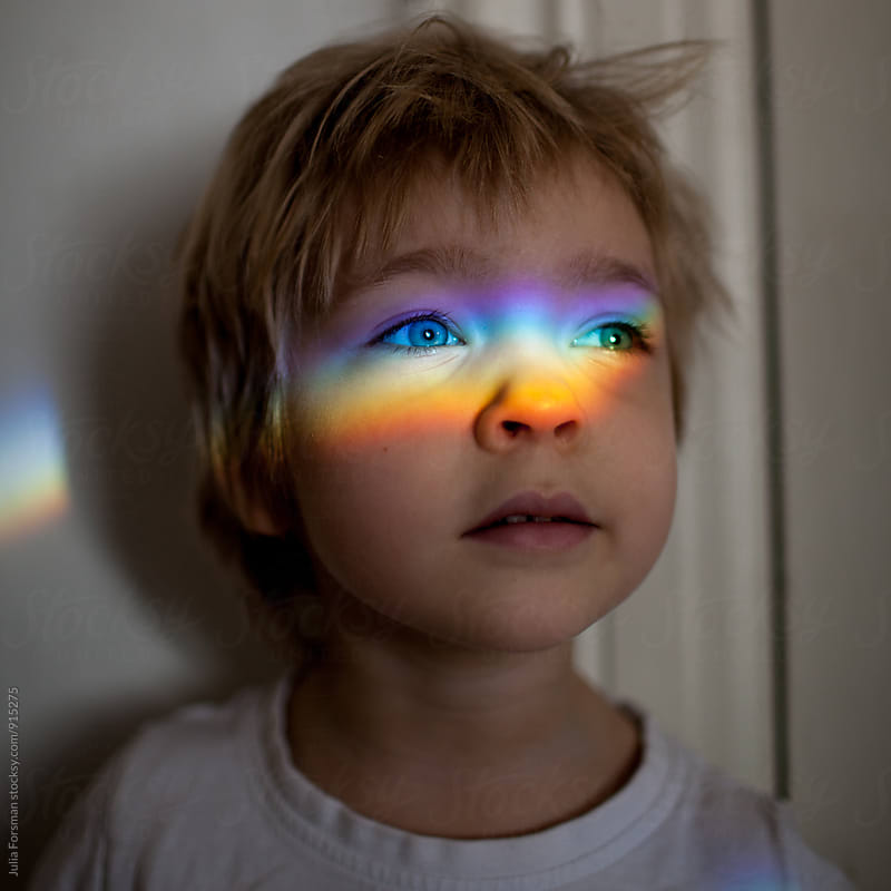 Confident child with a rainbow of light across her eyes. by Julia Forsman for Stocksy United