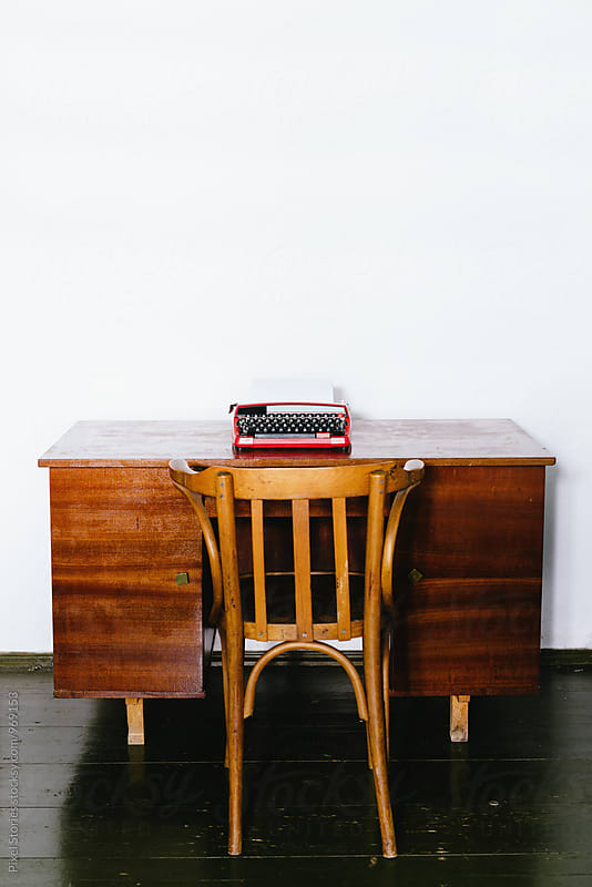 Vintage red typewriter on wooden desk by Pixel Stories for Stocksy United