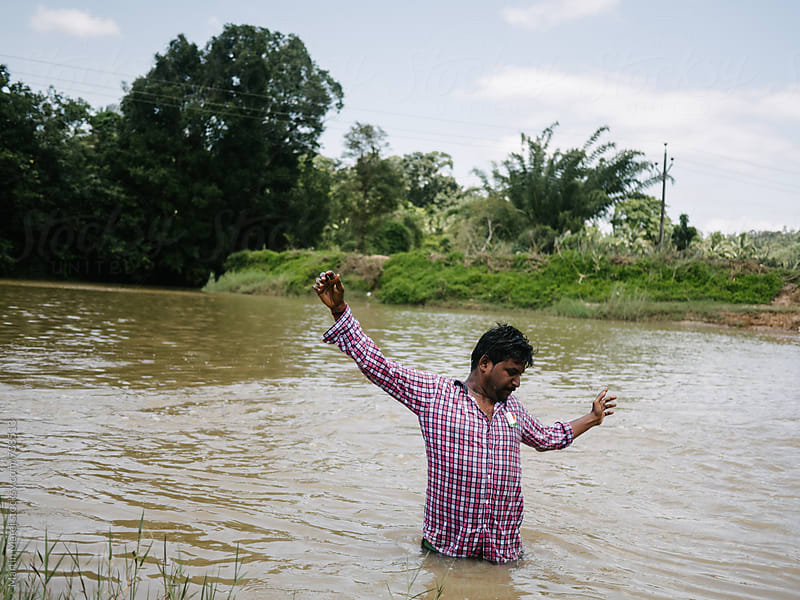 Indian drunken man standing in dirty river by Martin Matej for Stocksy United