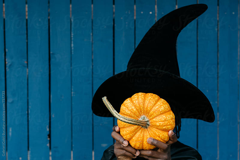 Black girl in witch Halloween costume holding a pumpkin by Gabriel (Gabi) Bucataru for Stocksy United