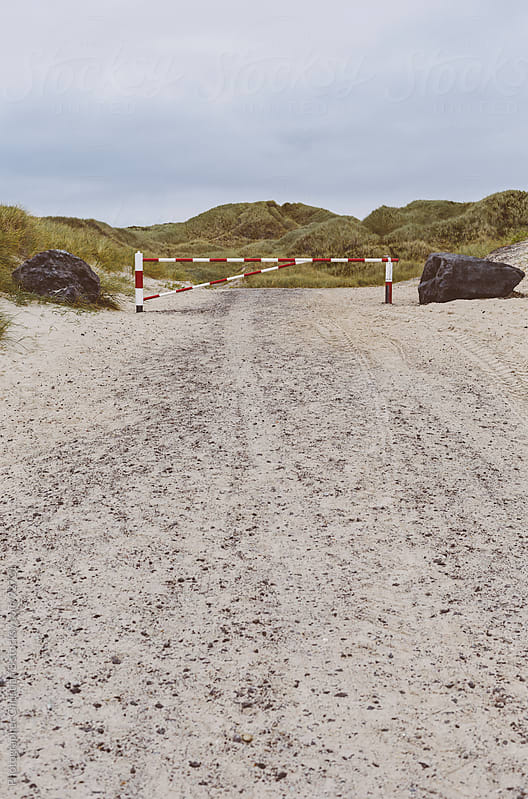 Stop barrier in front of grassy dunes by Photographer Christian B for Stocksy United