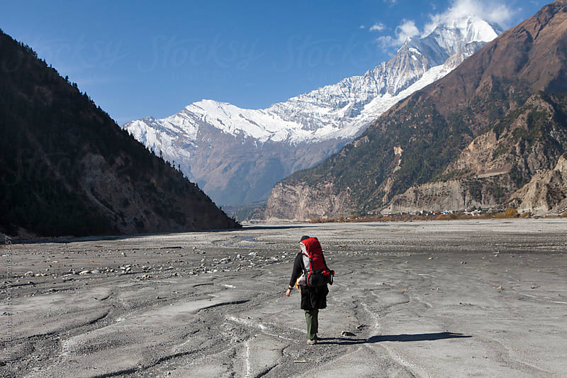 Young trekker in the himalayas crossing the river trekking in the himalayas. by Shikhar Bhattarai for Stocksy United