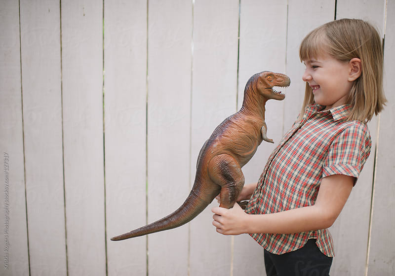 young girl playing with her toy dinasour by Kristin Rogers Photography for Stocksy United