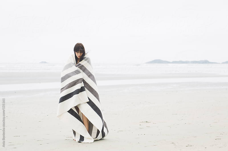 A woman wrapped in a striped blanket standing on a beach by Ania Boniecka for Stocksy United