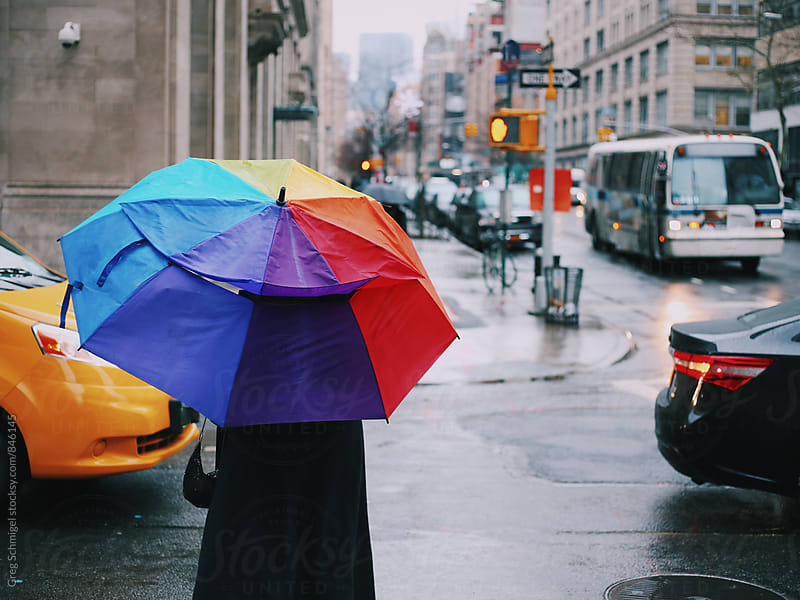 A person walking with a colorful rainbow umbrella on a rainy New York City street by Greg Schmigel for Stocksy United