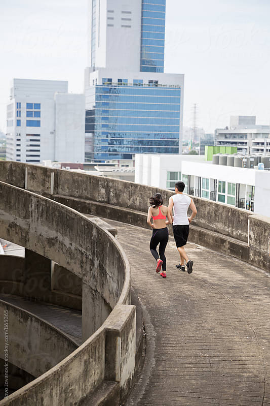 Backs of a handsome young couple jogging together in an urban environment  by Jovo Jovanovic for Stocksy United