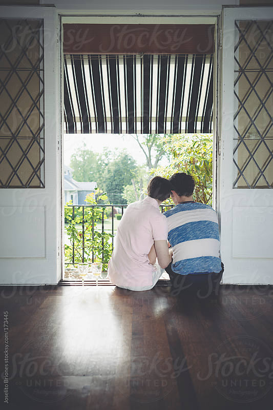 Male Gay Couple Sitting in the Balcony of their Home looking out to the garden by Joselito Briones for Stocksy United