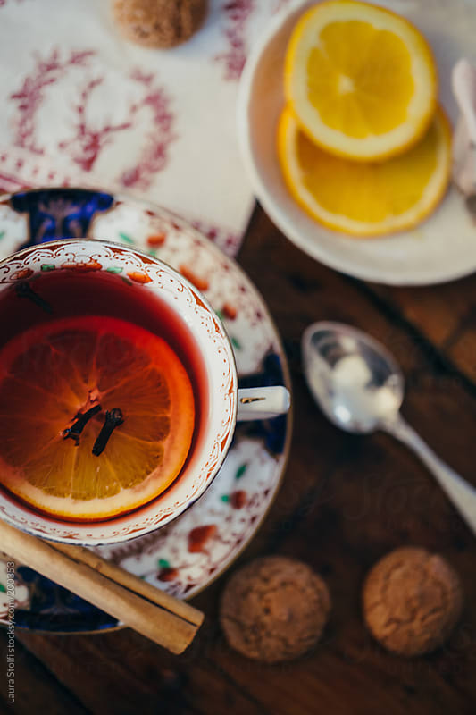 Winter break: spicy red tea with cinnamon sticks, lemon slice, cloves and cookies by Laura Stolfi for Stocksy United