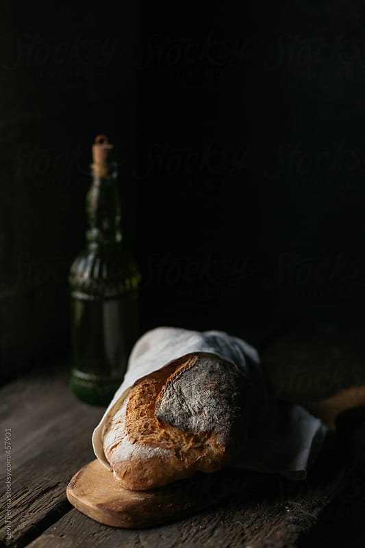 Fresh loaf of artisan bread on cutting board by Levi Tijerina for Stocksy United