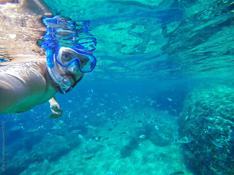 Man snorkeling in crystal clear waters by ACALU Studio for Stocksy United