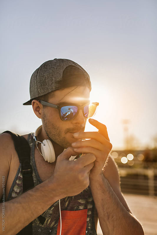Young Trendy Man Lighting a Cigarette at Sunset by Victor Torres for Stocksy United