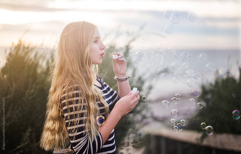 Girl blowing bubbles at the beach at sunset by Angela Lumsden for Stocksy United