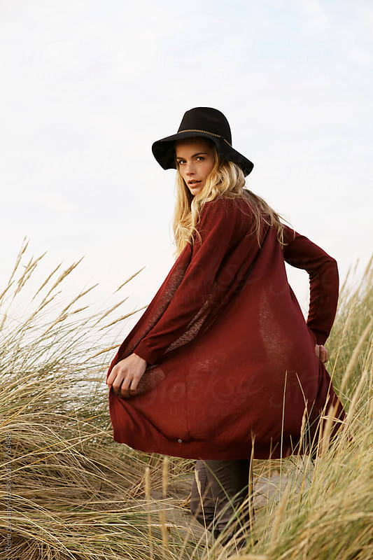 young woman with hat in dunes by Rene de Haan for Stocksy United