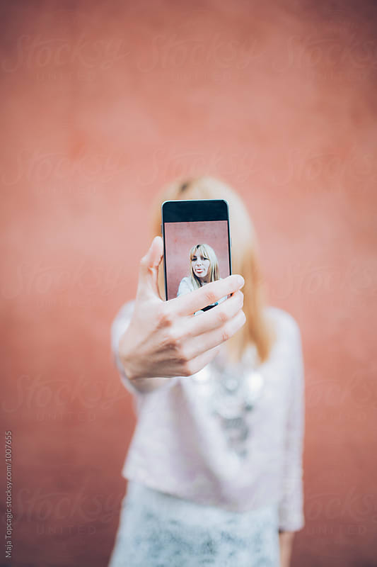 Beautiful blonde in front of a pink wall by Maja Topcagic for Stocksy United