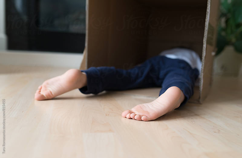 child resting face down inside a box by Tara Romasanta for Stocksy United