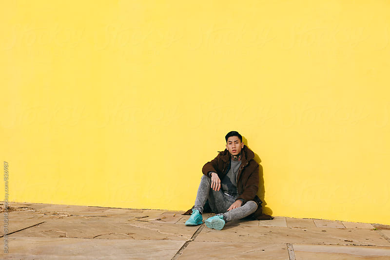 Portrait of an asian man sitting in front of a yellow wall. by BONNINSTUDIO for Stocksy United