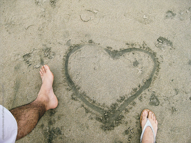 Heart drawn on beach sand with couple feet by Alejandro Moreno de Carlos for Stocksy United
