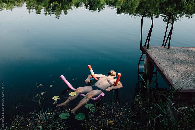 Caucasian Man Floating on Swimming Noodles in a Lake by Nemanja Glumac for Stocksy United