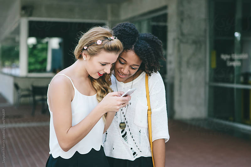 Two Young Women Looking at Smart Phone by Stephen Morris for Stocksy United