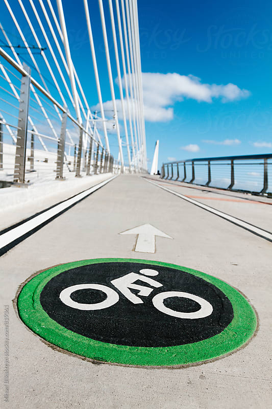 Bright painted bycicle sign and arrow painted on a bike lane on a bridge by Mihael Blikshteyn for Stocksy United