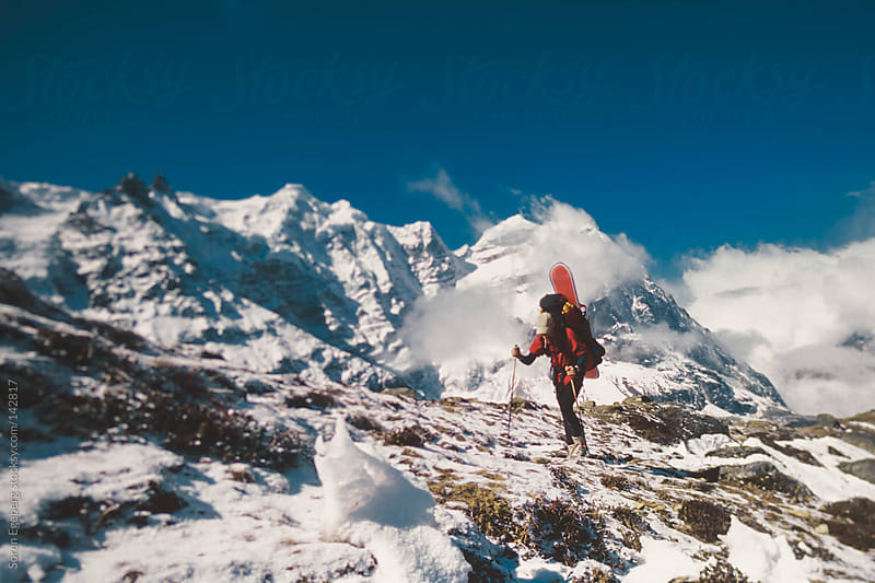 Climber hiking with backpack and snowboard in the Himalaya mountains of Nepal. by Soren Egeberg for Stocksy United