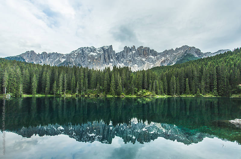Crystal blue lake in the Dolomite mountains of Italy by Maximilian Guy McNair MacEwan for Stocksy United