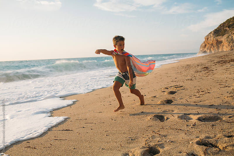 Boy playing on the beach. by Dejan Ristovski for Stocksy United
