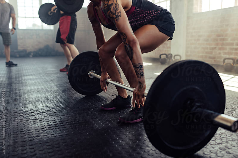 Tattooed woman lifting barbell at gym by Jacob Lund for Stocksy United