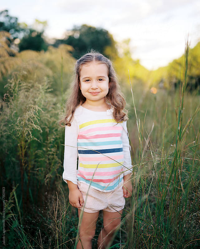 Portrait of a beautiful young girl playing in a field of tall grass by Jakob for Stocksy United