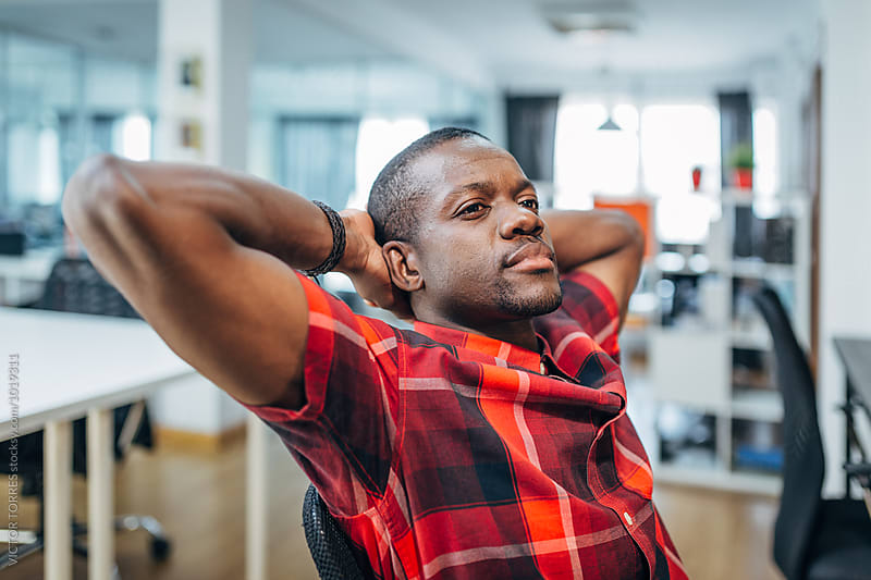 Portrait of a Pensive Black Man Relaxing at the Office by Victor Torres for Stocksy United