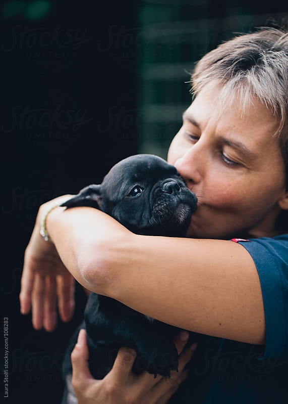 Woman holding in her arms and cuddling a French Bulldog puppy dog by Laura Stolfi for Stocksy United